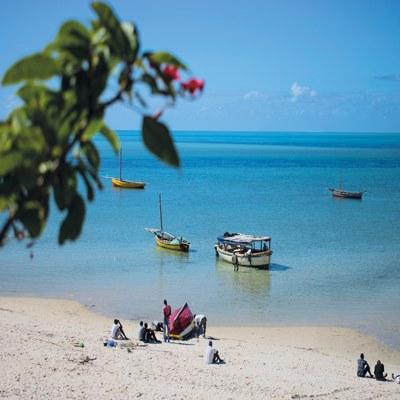 Strand Mosambik mit Einheimischen und Booten