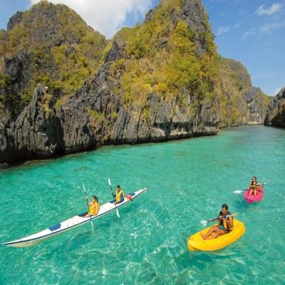 Kajak fahren in glasklarer, türkisgrüner Bucht auf den Philippinen