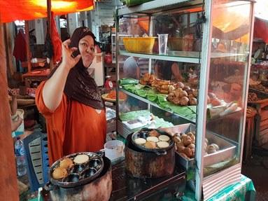 buntes Marktreiben: Frau verkauft Spezialitäten